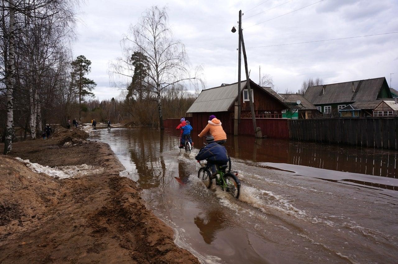 Дети катаются на велосипедах по затопленной улице братьев Даниловых